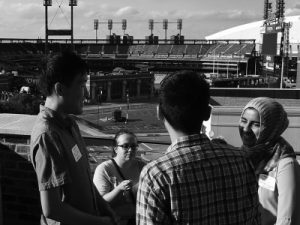 Black and white photo of interns conversing amongst each other outside in the sun