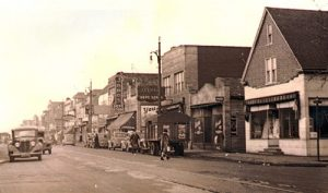 An old image of a street in Detroit with old stores and cars lining the road