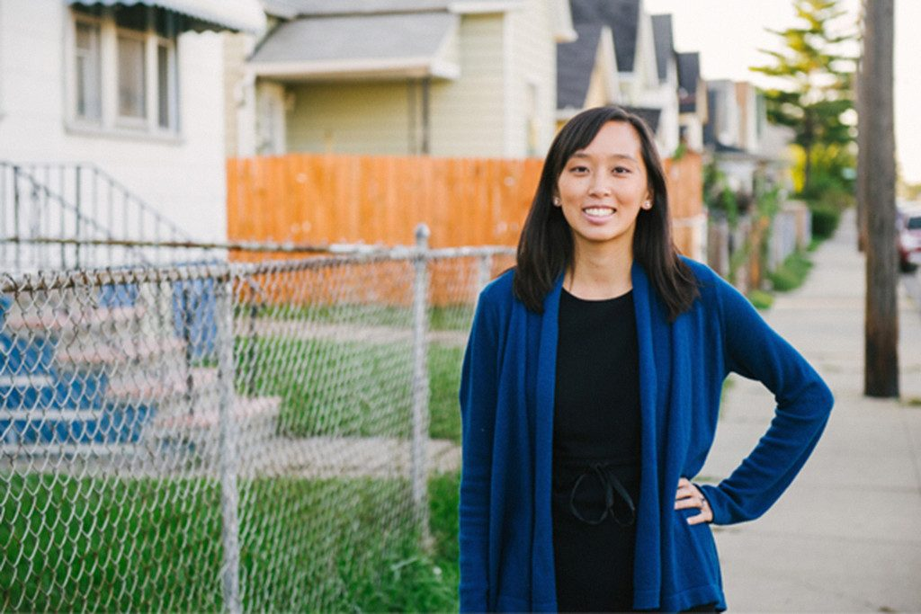 Stephanie Gray Chang poses in front of a row of houses.