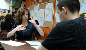 Elizabeth Moje sits across from a male students, speaking and gesturing with her hands.