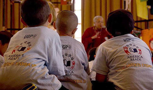 Children wearing matching t-shirts sit in the Ginsberg Center listening to a woman speak.