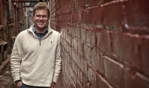 Josh Newell leans against a brick wall, smiling and wearing a white quarter-zip jacket