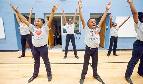 "Several children wearing ""I heart dance"" t shirts smile widely and raise their arms in the air in the form of a ""V"""