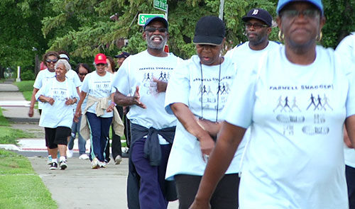 Members of the walking group wearing matching t shirts walk down a sidewalk together in good spirits, some in the foreground and some in the background.