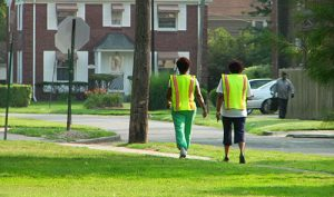 Two women walk on a sidewalk next to a grassy lawn wearing bright yellow vests.