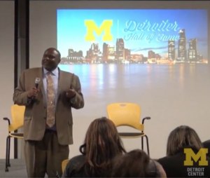 Man stands in front of projected image of Detroit skyline, speaking into microphone in front of audience.