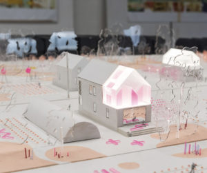 Paper model of a neighborhood, including trees, houses and farm land.
