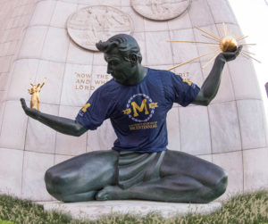 Statue of a man sitting cross-legged holding a sun in his right hand wearing a blue t-shirt with a block M on it.