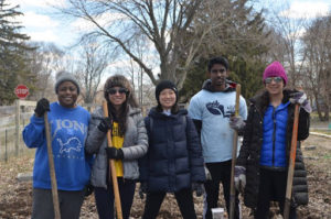 Five volunteers stand outdoors, dressed in hats and coats, holding rakes, and smiling.