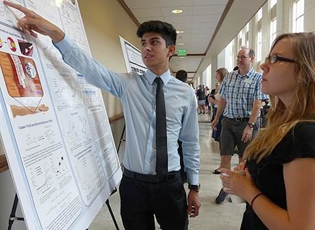 Student presenting poster to a peer