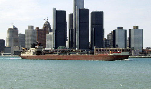 The Detroit skyline, with a large cargo ship in front of the buildings.