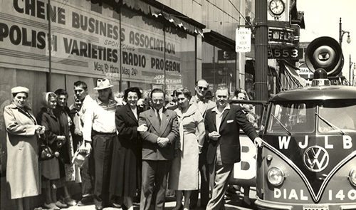 Old photo of a group of people outside of the Chene Business Association/Polish Varieties Radio Program, next to a Volkswagen bus