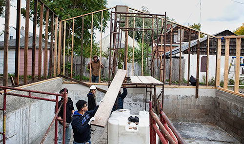 Afterhouse participants work to repurpose a burned-out house, standing in the framework and foundation of the house.