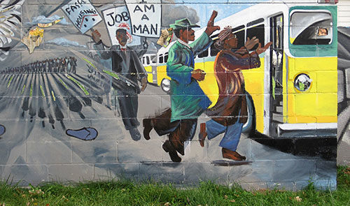 Mural depicting line of people getting on a bus, with some of the line holding signs.
