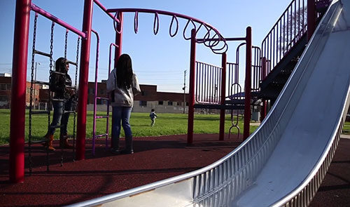 Two girls stand on a playground next to monkey bars.