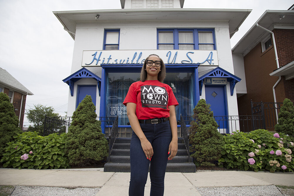 "Jefferson, wearing a ""Motown Studio A"" t-shirt, stands in front of a small blue and white house adorned with a sign reading ""Hitsville, U.S.A."""