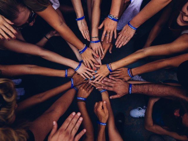 "A circle of many people wearing ""Emfasis"" bracelets outstretch their hands to meet in the center of the circle."
