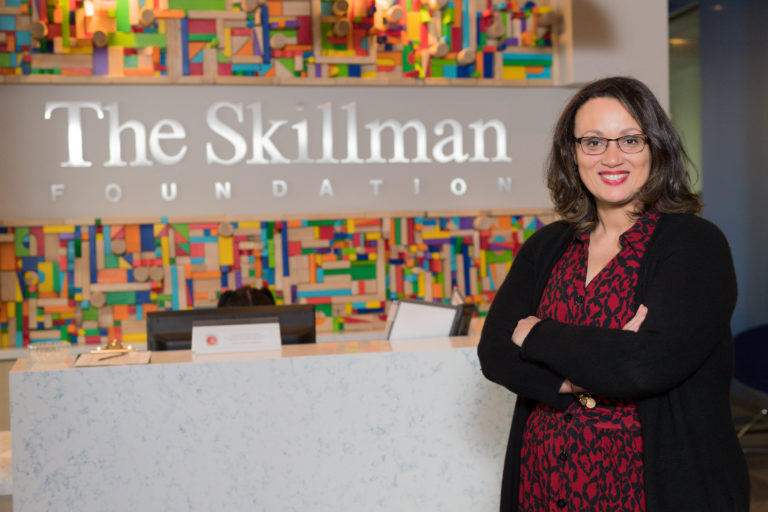 Tonya poses with arms folded and a smile in front of the Skillman Foundation's colorful sign.